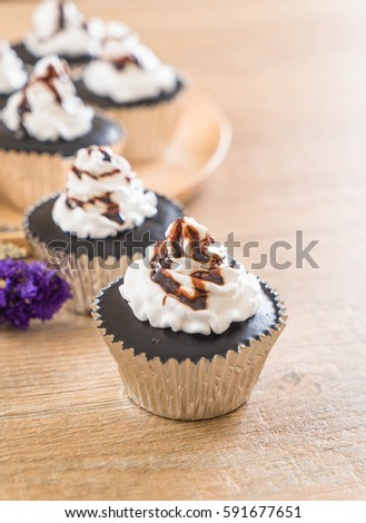 chocolate cup cake with whipped cream on table #591677651
