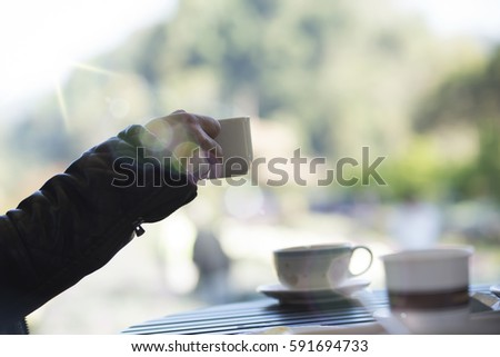 businessman and a cup of coffee in hand, blank text and soft focus blur #591694733