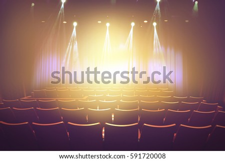 vintage theater with lighting spot on stage before showtime , empty auditorium with seats #591720008