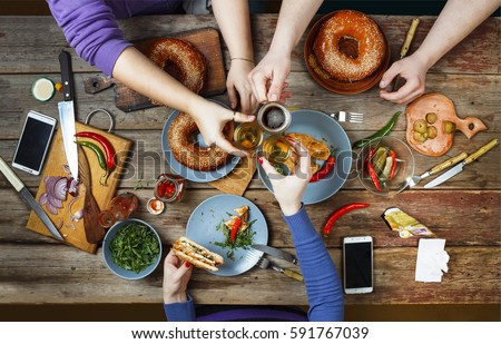Friends Happiness Enjoying Dinning Eating Concept. Happy meeting friends at a dinner party. Enjoying dinner. Top view of group of people having dinner together while sitting at the rustic wooden table #591767039