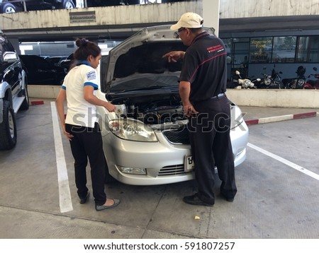 Rayong  Thailand , March 3 - 2017 : Thai woman check engine with service man in TOYOTA showroom after service. #591807257