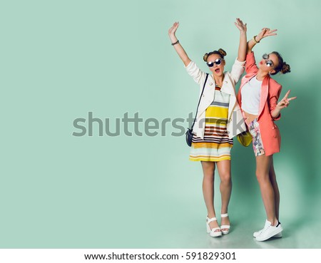 Full height image  of two happy cheeky girls  , best friends having fun , laughing on blue background. . Wearing stylish  casual jackets, striped pop dress. Space for text.  Royalty-Free Stock Photo #591829301