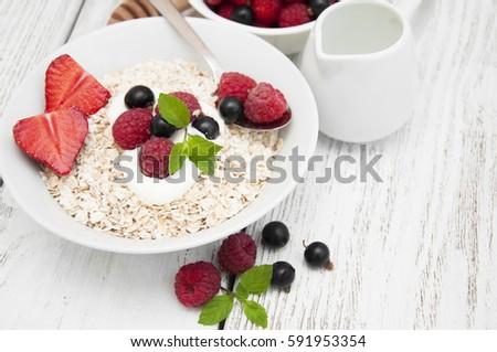 Morning breakfast - cereal, yogurt, fresh berries and honey on wooden background #591953354
