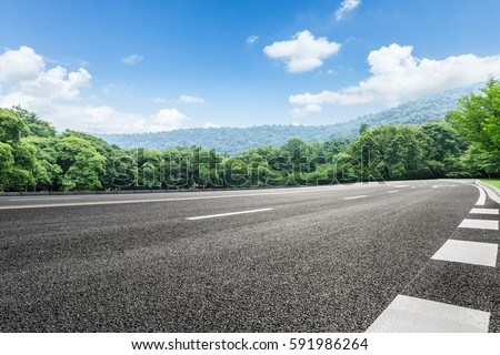 Asphalt highways and mountains under the blue sky Royalty-Free Stock Photo #591986264