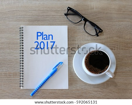 PLAN 2017 CONCEPT NOTEBOOK WITH COFFEE CUP ON TABLE #592065131