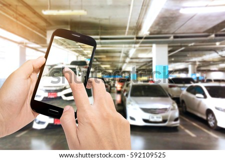 Taking a picture with a smart phone in abstract blur parking car indoor with sunshine background, Color tone effect.