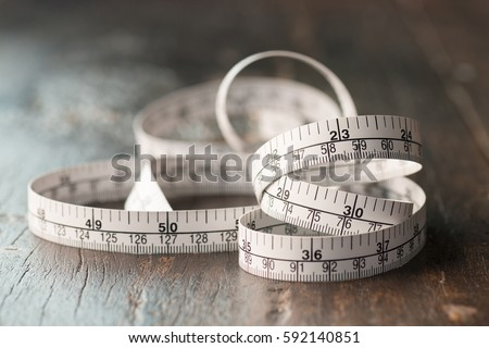 Close up tailor measuring tape on wooden table background. White measuring tape shallow depth of field. #592140851
