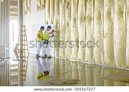 Zrenjanin, Vojvodina, Serbia - June 29, 2015: Workers are assembly gypsum wall. Plasterboard is under construction using wooden ladder. #592167227