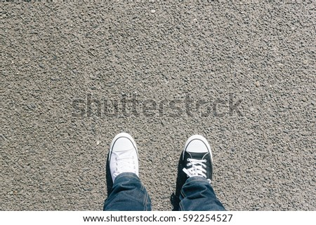 Pair of legs, different black and white shoes on asphalt ground, high angle footsie or flortrait, personal pespective from above. #592254527