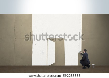 A business man draws a opened door on a concrete barrier. #592288883