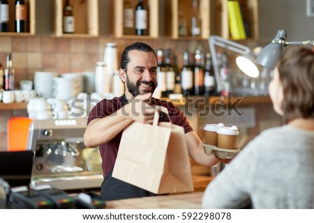 small business, people, takeaway and service concept - happy man or waiter giving bag and paper cups with hot drinks to customer at coffee shop #592298078