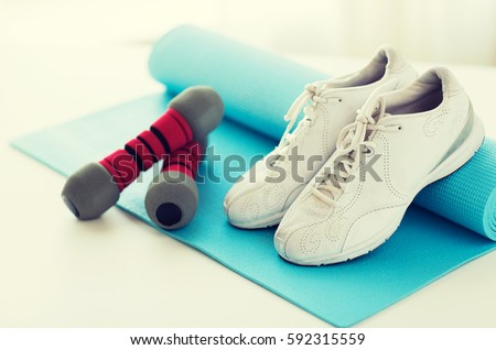 sport, fitness, healthy lifestyle and objects concept - close up of sneakers, dumbbells and sports mat #592315559
