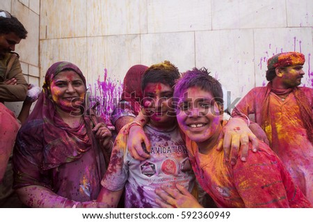 NANDGAON, INDIA, 18 MARCH 2016 : Unidentified people with face smeared with colors participate in the holi celebration at Krishna temple, . Holi is the most celebrated religious festival in India. #592360949