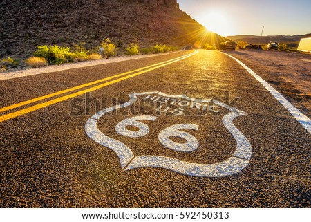 Street sign on historic route 66 in the Mojave desert photographed against the sun at sunset Royalty-Free Stock Photo #592450313