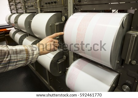Seismograph records an earthquake on the sheet of measuring paper. Seismological device for measuring earthquakes. Earthquake wave on graph paper. Human finger showing a detail of the earthquake. #592461770