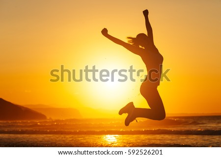 Silhouette of happy joyful woman jumping and having fun at the beach against the sunset. Freedom and leisure vacation concept. Royalty-Free Stock Photo #592526201