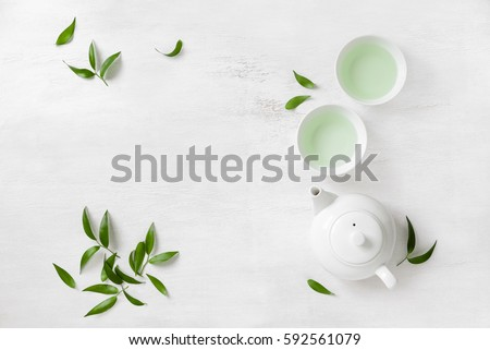 Tea concept, two white cups of tea and teapot surrounded with green tea leaves, view from above, space for a text #592561079