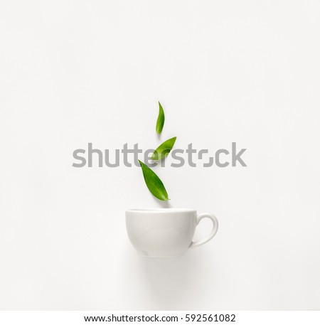Cup of fresh green tea with green leaves rising above, tea aromatic qualities concept #592561082