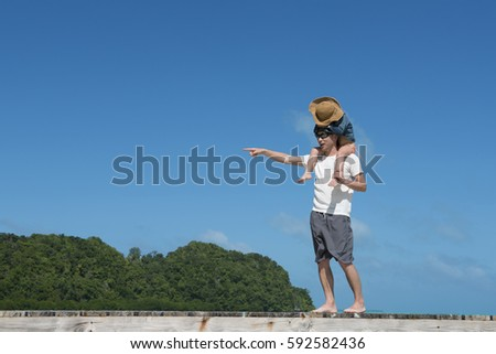 Father and daughter walking with a shoulder wheel on the beach #592582436