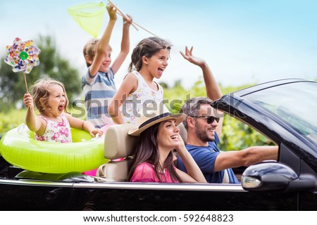 A joyful family, in a convertible car, goes on holiday to the sea. Children have colorful buoys and landing nets. Focus on the mother Royalty-Free Stock Photo #592648823