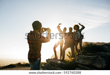 Group of young friends hiking on mountain on a summer day. Young man taking a photo of his friends.