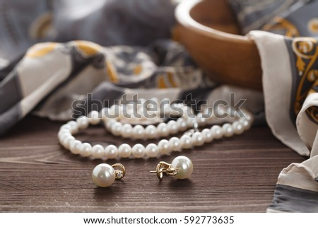 Womans morning scene with pearl lay on silk shawl