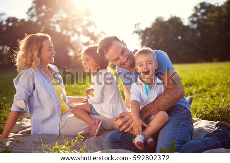 Young family with children having fun in nature  Royalty-Free Stock Photo #592802372