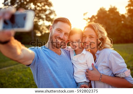 Smiling man and woman with young son taking photo #592802375