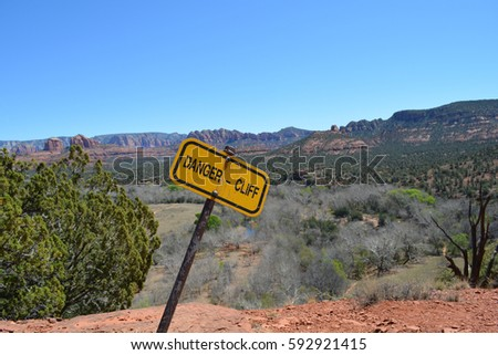 """A yellow warning sign on a hiking trail in Sedona, Arizona, in the American Southwest, that cautions travelers: """"DANGER - CLIFF"""""""