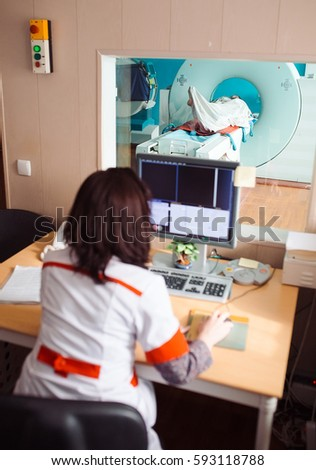 MRI machine and screens with doctor and nurse #593118788