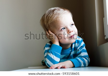 Portrait of little, dreamy, lost in thoughts and cheerful two years old boy #593158601