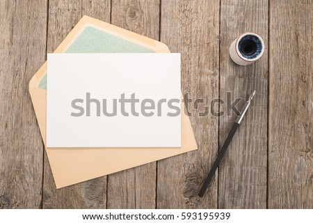 Envelope, ink pen, inkwell on a wood table Royalty-Free Stock Photo #593195939
