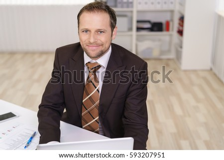 Friendly businessman looking up with a smile as he sits at his desk in the office working on a laptop computer #593207951