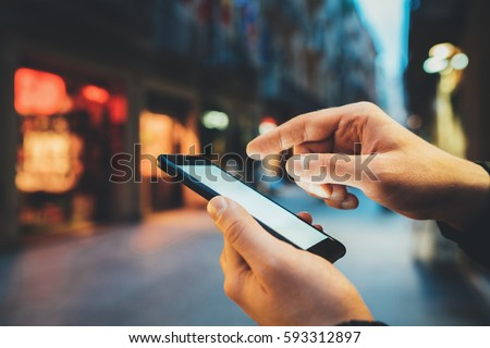 Closeup of male hands using smartphone with blank screen with copy space for design or text message, young man typing an sms message at social networks outdoor, evening city streets in the background #593312897
