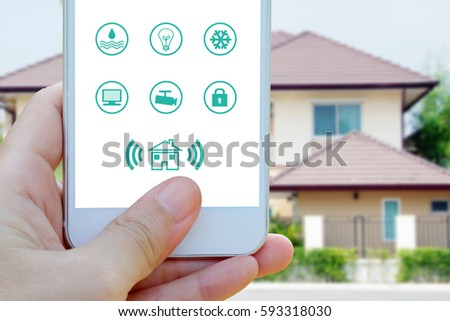 Hand using smart phone with smart home control application on screen over blurred house background, smart home concept  #593318030
