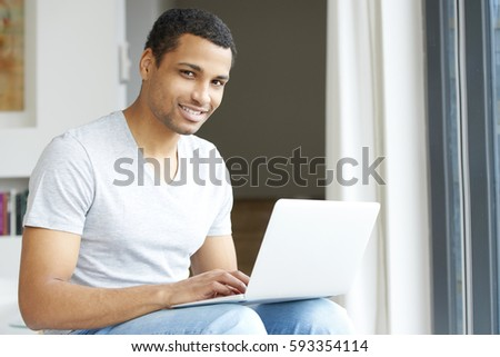 Shot of a handsome young man using his laptop while relaxing at home. #593354114