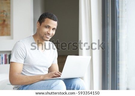 Shot of a handsome young man using his laptop while relaxing at home. #593354150