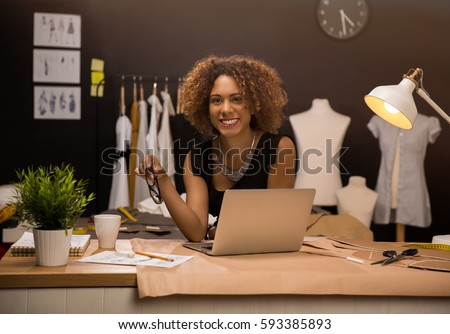 Two young entrepreneur women, and fashion designer working on her atelier Royalty-Free Stock Photo #593385893