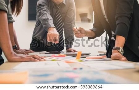 Brainstorming Group of people Working Concept. Business team brainstorming. Marketing plan researching. Paperwork on the table, laptop and mobile phone. Royalty-Free Stock Photo #593389664