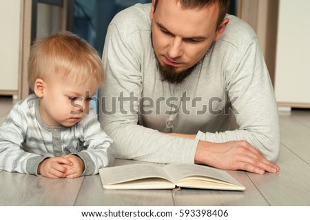 Father and son lying at sofa, they are reading a book. #593398406