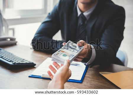 Businessman giving money to his partner while making contract - bribery and corruption concepts #593433602