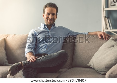 Portrait of handsome man looking at camera and smiling while sitting on couch at home #593478407