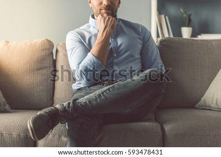 Cropped image of handsome man sitting on couch at home #593478431