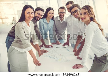 Business people are examining documents and smiling during the conference
