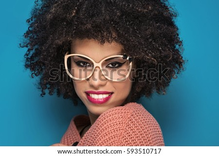 Attractive young African American girl with afro hairstyle and glamour makeup posing in fashionable sweater on blue background. #593510717