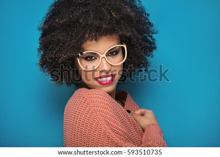 Attractive young African American girl with afro hairstyle and glamour makeup posing in fashionable sweater on blue background. #593510735