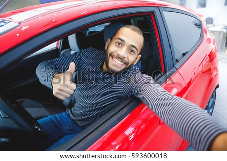 First car pic. Handsome young African man smiling making a selfie sitting in his new car at the dealership copyspace owner ownership driver mulatto buyer consumerism lifestyle travel concept