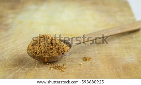 Wooden spoon of natural spice for meat on a kitchen board with scratches