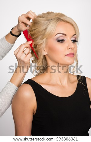 Hairdresser makes hair styling blond girl in a beauty salon #593806061