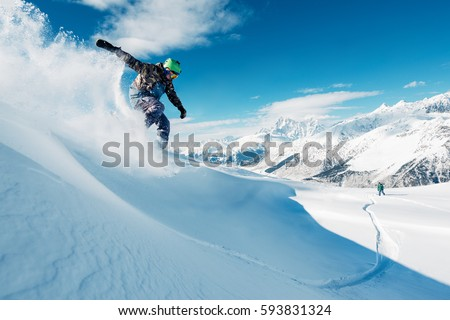 snowboarder is riding with snowboard from powder snow hill or mountain very fast #593831324